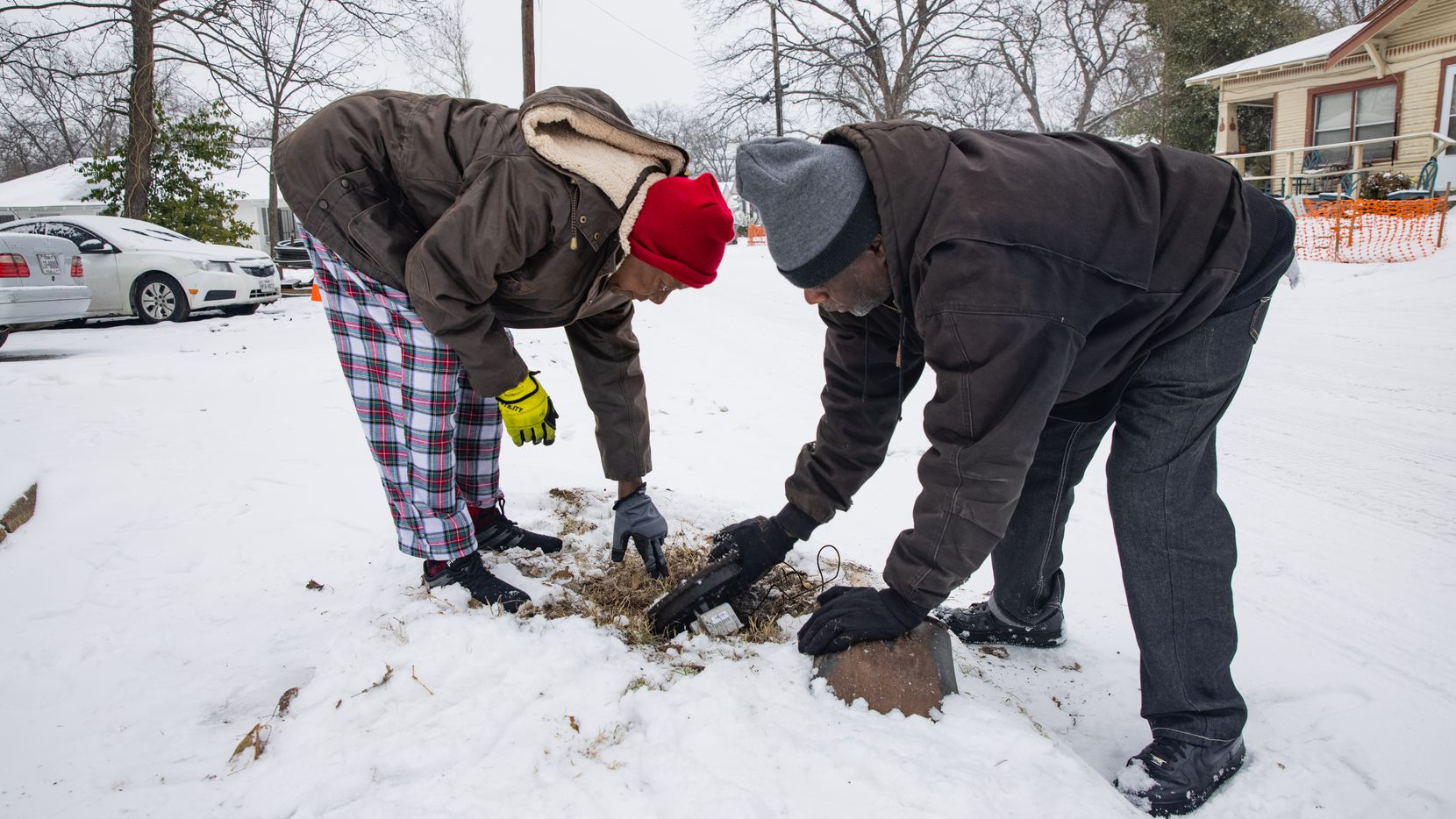 Patricia Broadway (left) and Leon Morris put the cover back after shutting the water off in Broadway's home in East Dallas on Feb. 17, 2021. Broadway noticed a pipe busted under her kitchen even though she said she did everything right.