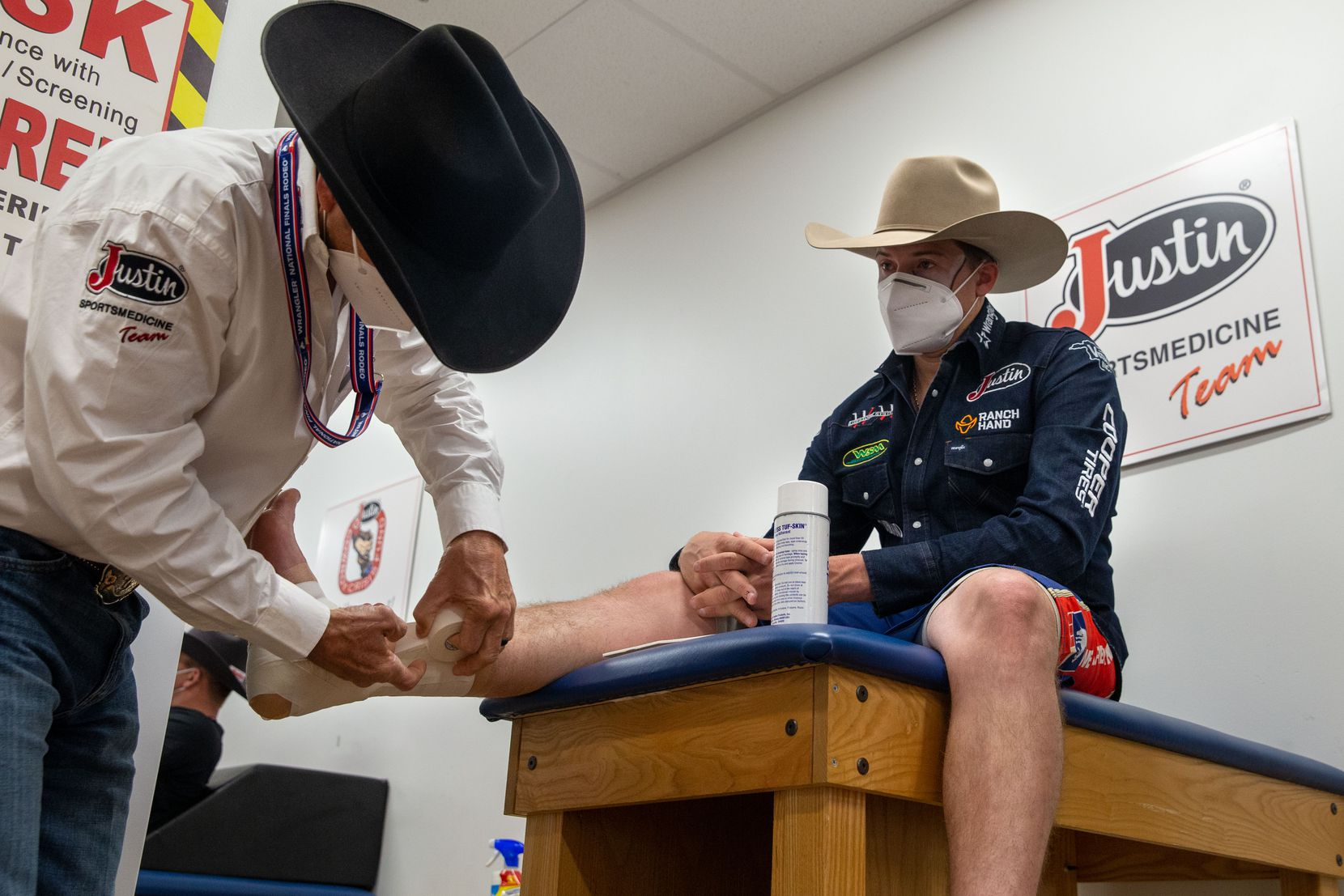 "Bullfighter Cody Webster (right) has his ankles taped by sports medicine team program director Rick Foster ahead of the bull riding event during the sixth night of the National Finals Rodeo at Globe Life Field in Arlington, Texas, on Tuesday, Dec. 10, 2020. Webster was named the Pro Rodeo Cowboys Association Bullfighter of the Year for 2020 on the opening day of the NFR. ""He's taking care of our bull riders, so we take care of him,"" Foster said. (Lynda M. González/The Dallas Morning News)"