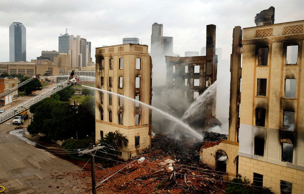 A Dallas firefighter mans an aerial hose to douse the fire at the Ambassador Hotel just south of downtown Dallas, May 28, 2019. Over 100 firefighters responded to the four-alarm fire.
