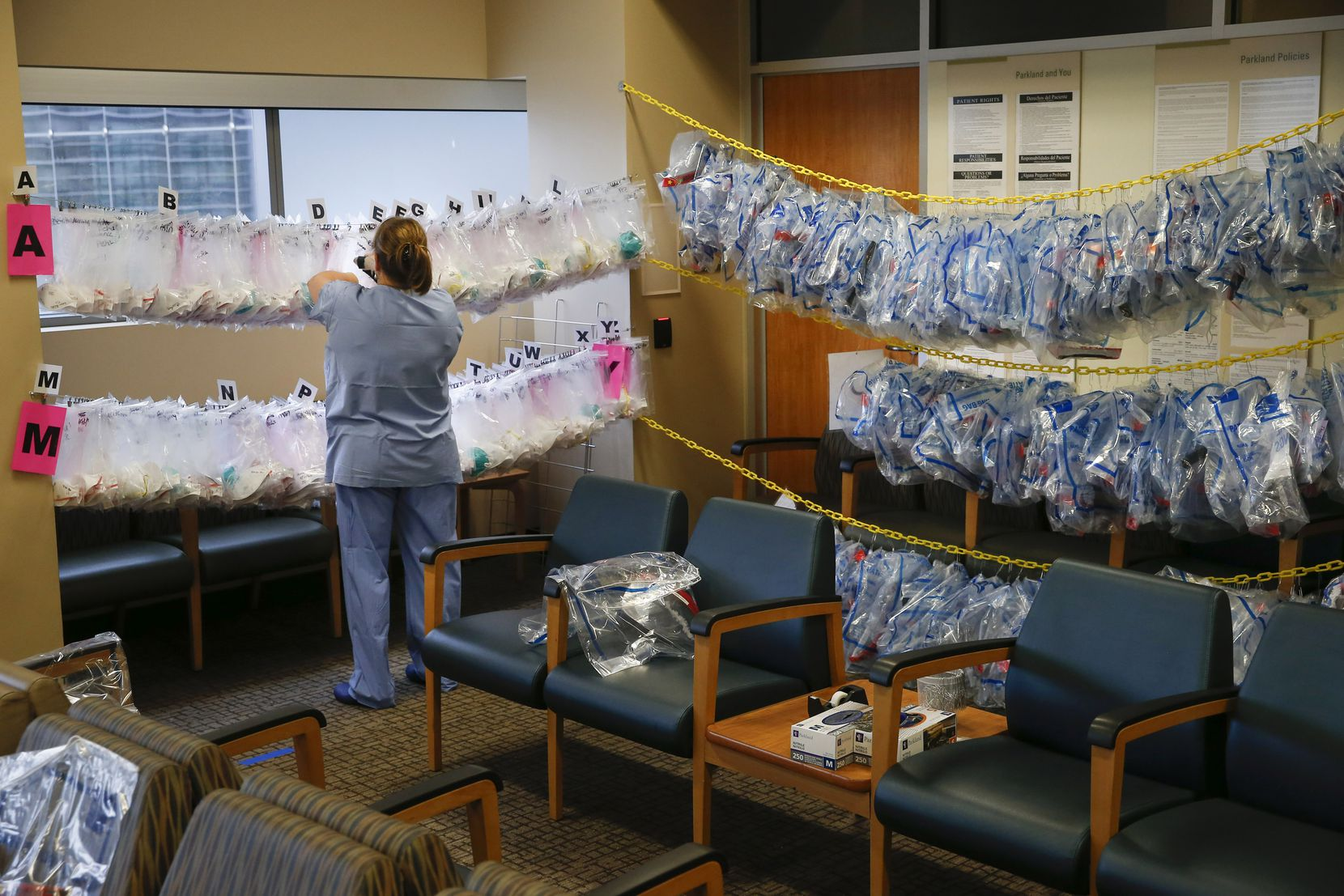 In what during normal times is the OR waiting room, now converted to a check-in station for staff working in the COVID-19 Tactical Care Unit, nurse Victoria Dart organizes sanitized N-95 masks and face shields for reuse by their original user at Parkland Memorial Hospital.