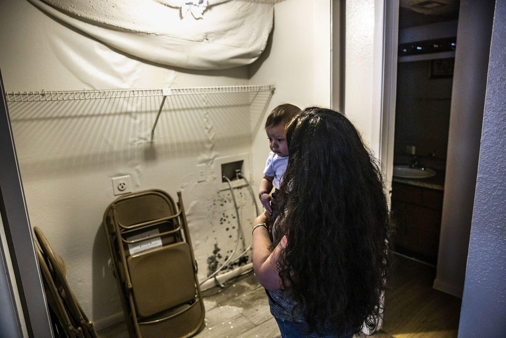 María Magarin, con su bebé en brazos, muestra el moho que ya se ha formado en su apartamento que sufrió daños por que se inundó. Desde la tormenta de febrero no tiene agua caliente.
