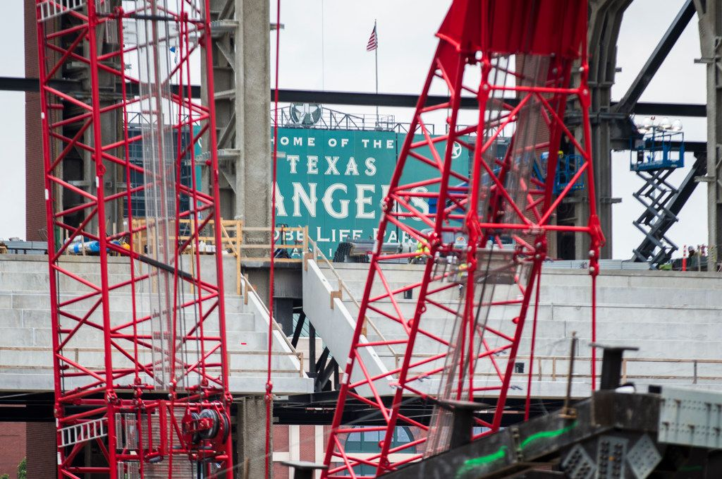 """A """"Home of the Rangers"""" sign at Globe Life Park is seen through construction cranes at Globe Life Field on Wednesday, June 19, 2019 in Arlington. (Ashley Landis/The Dallas Morning News)"""