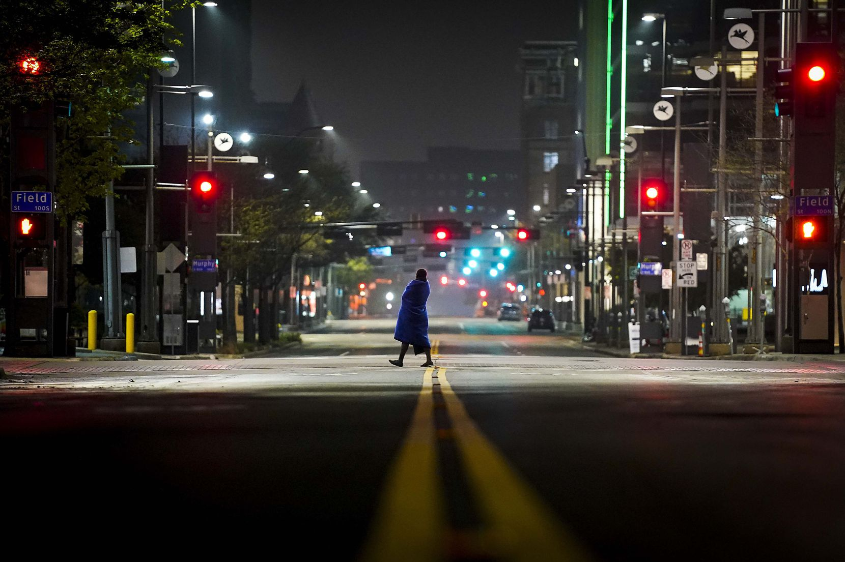 A solitary figure crosses the empty intersection of Main and Field streets in downtown Dallas at around 12:30 a.m. on Tuesday, March 24, 2020. Dallas County's shelter-in-place order went into effect at 11:59 p.m. on Monday, requiring all people living in Dallas County to stay home — except for essential activities and jobs.