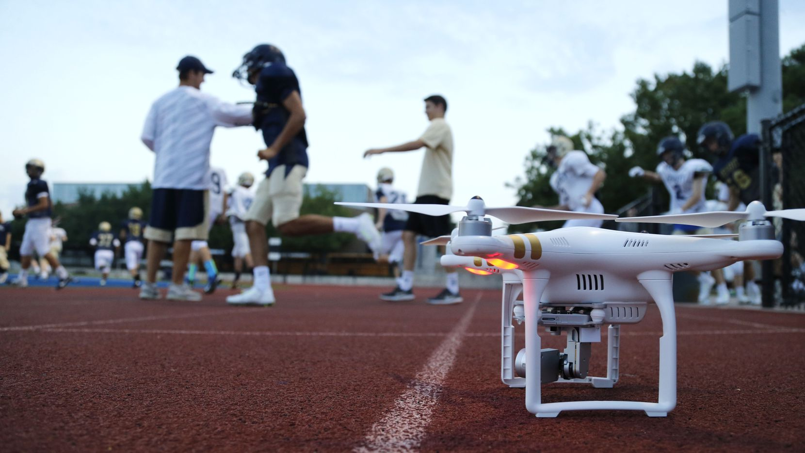 Jesuit football played take the field as a drone is powered up before football practice at Jesuit College Preparatory School of Dallas in Dallas, on Tuesday, August 25, 2015. (Vernon Bryant/The Dallas Morning News)