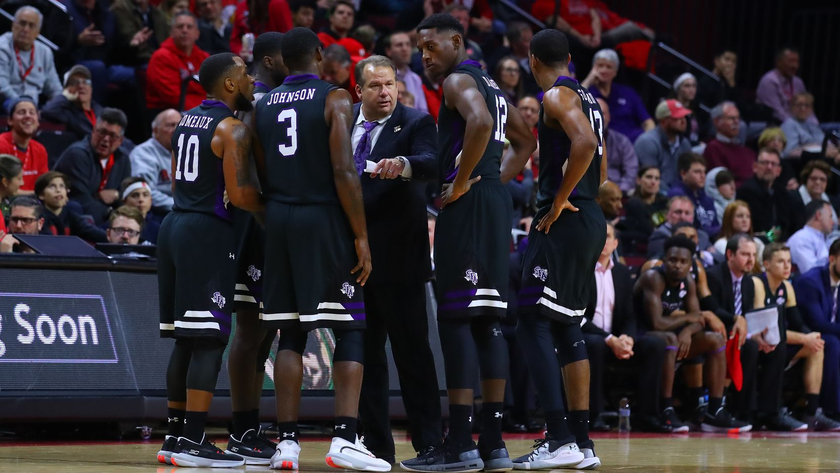 Stephen F. Austin head coach Kyle Keller (center) talks with his players during the second half of a game against Rutgers on Nov. 20, 2019, at Louis Brown Athletic Center in Piscataway, N.J. (Photo by Rich Graessle/Icon Sportswire via Getty Images)