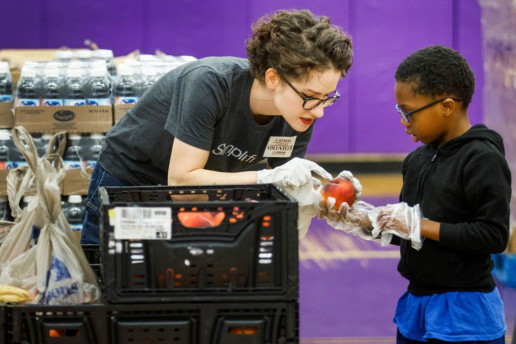Ashley Graham of Simpli.fi sorts produce while volunteering for the mobile food bank at the COMO Community Center on Friday, Aug. 18, 2017, in Fort Worth. (Smiley N. Pool/The Dallas Morning News)
