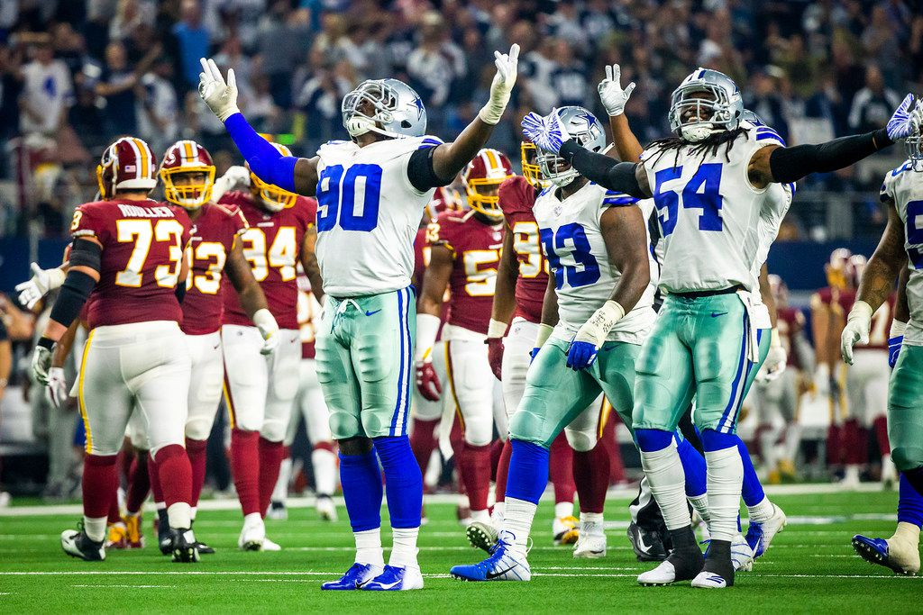 Dallas Cowboys defensive end Demarcus Lawrence (90) celebrates with middle linebacker Jaylon Smith (54) after intercepting a pass by Washington Redskins quarterback Colt McCoy (12) during the second half of an NFL football game at AT&T Stadium on Thursday, Nov. 22, 2018, in Arlington.