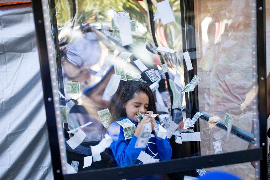Cynthia Mendoza, 10, of Dallas plays in the cash booth during the Texas Latino Gay Pride 2016 at Reverchon Park on Saturday.