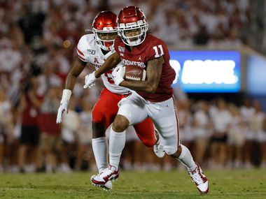 Oklahoma wide receiver Jadon Haselwood (11) runs ahead of Houston linebacker Jordan Carmouche (8) during the second half of an NCAA college football game in Norman, Okla., Sunday, Sept. 1, 2019. Oklahoma won 49-31.
