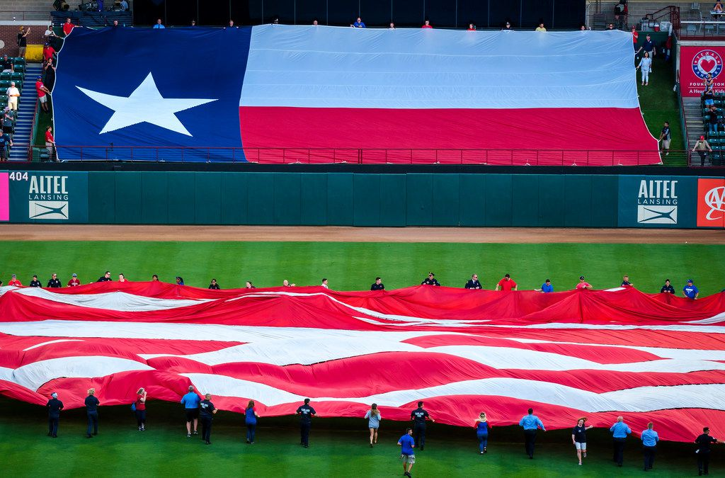 First responders from the Arlington police and fire departments unfurl large US and Texas flags at Globe Life Park before a game between the Texas Rangers and the Tampa Bay Rays on Wednesday, Sept. 11, 2019, in Arlington. (Smiley N. Pool/The Dallas Morning News)