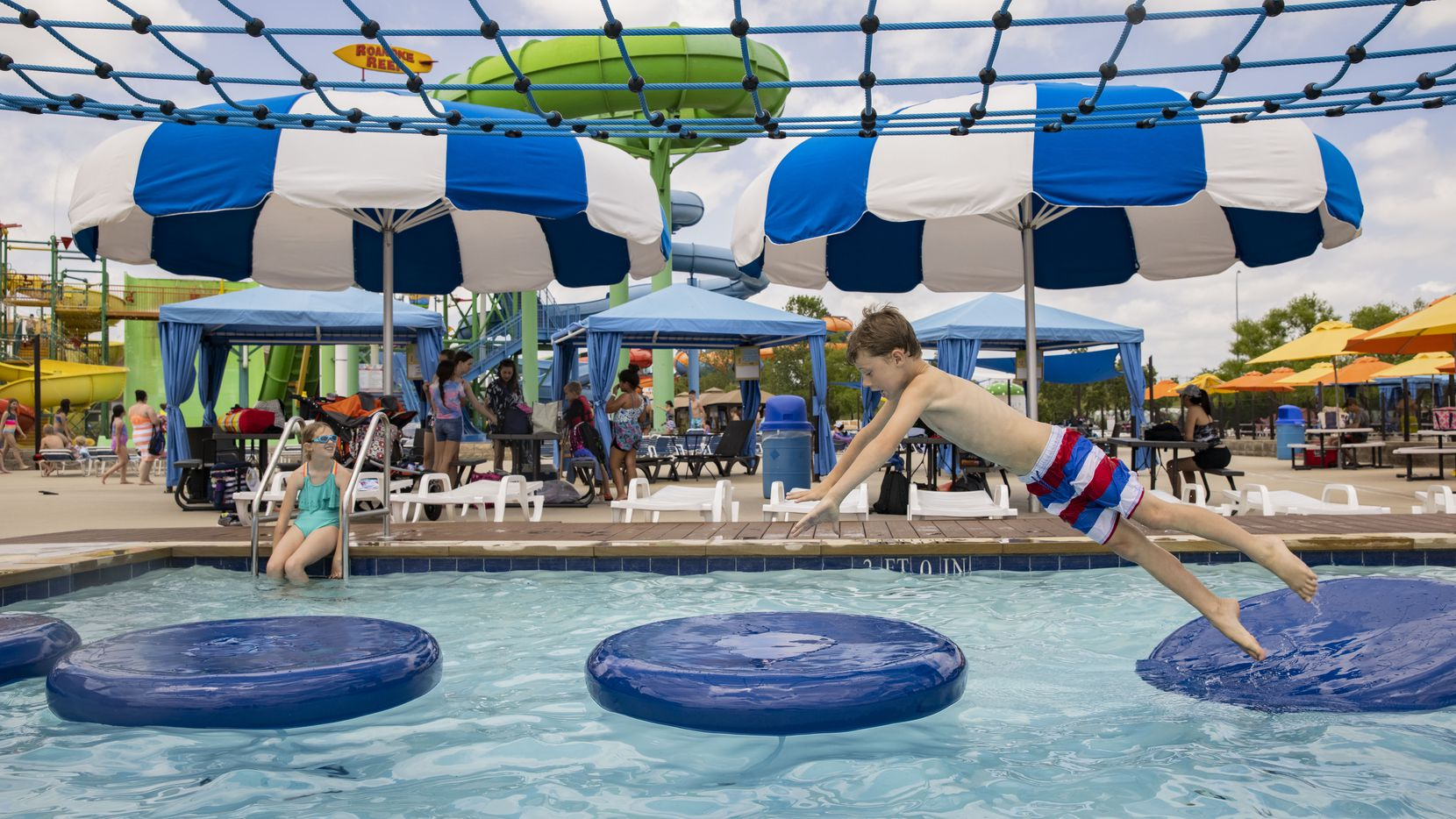 Rivers Garrett, 7, of Haslet jumps from pad to pad while trying out the Coconut Cove obstacle course at Hawaiian Falls in Roanoke.