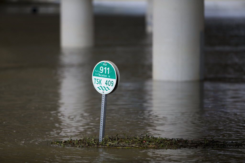 A sign on a trail along the Trinity River is seen surrounded by high river water on June 1, 2016 in Dallas. Flood stage is 30 feet but during this weather event water reached a little over 36 feet. (Ting Shen/The Dallas Morning News)