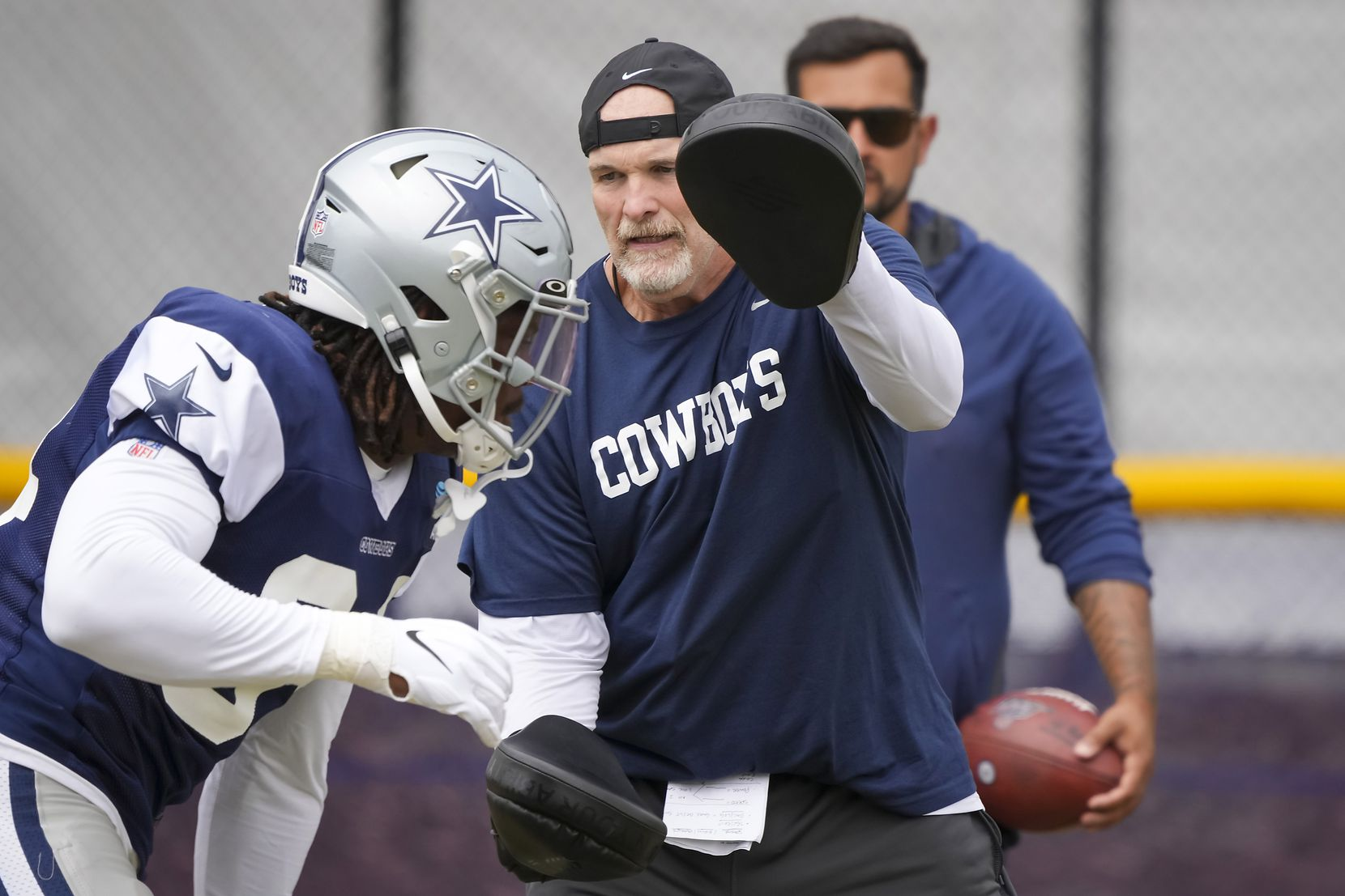 Dallas Cowboys defensive coordinator Dan Quinn works with defensive end Randy Gregory (94) during a practice at training camp on Saturday, July 31, 2021, in Oxnard, Calif.