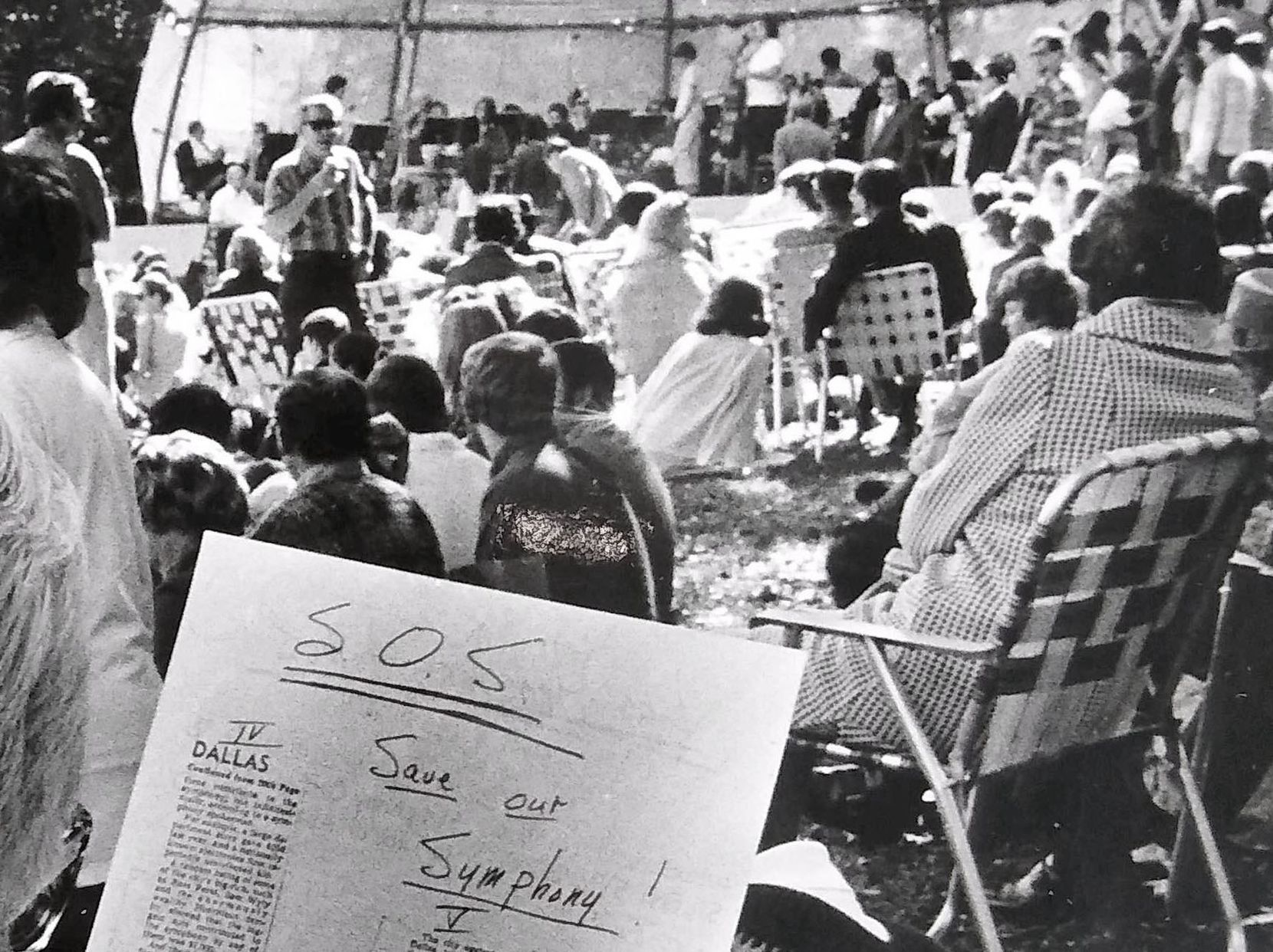 "In 1974, a Dallas Symphony Orchestra concert-goer reviews one of the ""SOS: Save Our Symphony"" appeals distributed among the 7,500-person Lee Park crowd during a concert at the park in Dallas."
