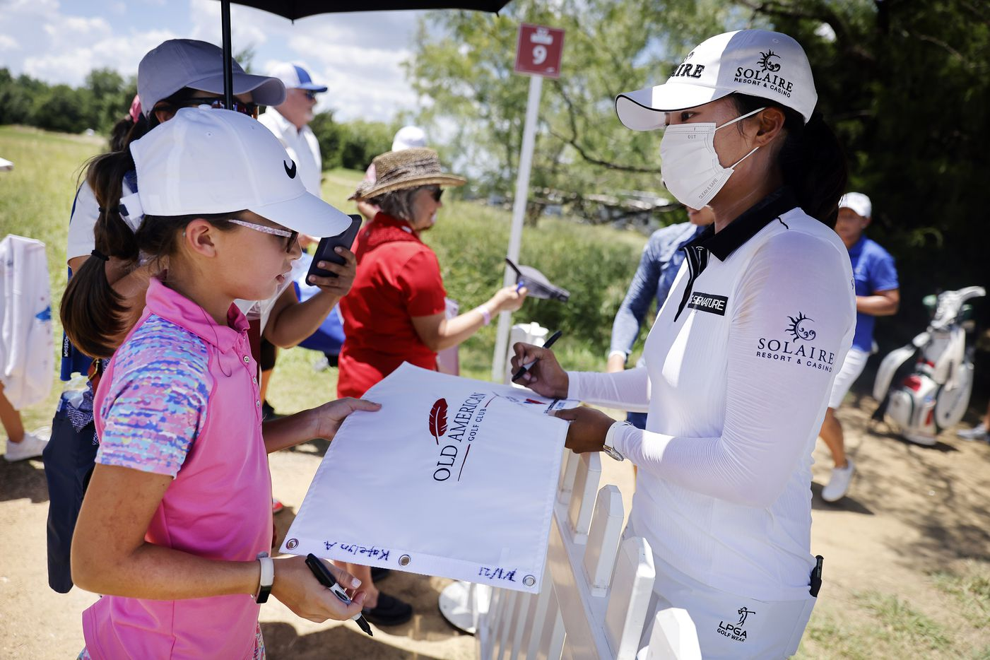 Professional golfer Jin Young Ko (right) signs a pin flag for Katelyn Allen of Montgomery, Texas after her opening round 8-under in the LPGA VOA Classic at the Old American Golf Club in The Colony, Texas, Thursday, July 1, 2021. (Tom Fox/The Dallas Morning News)