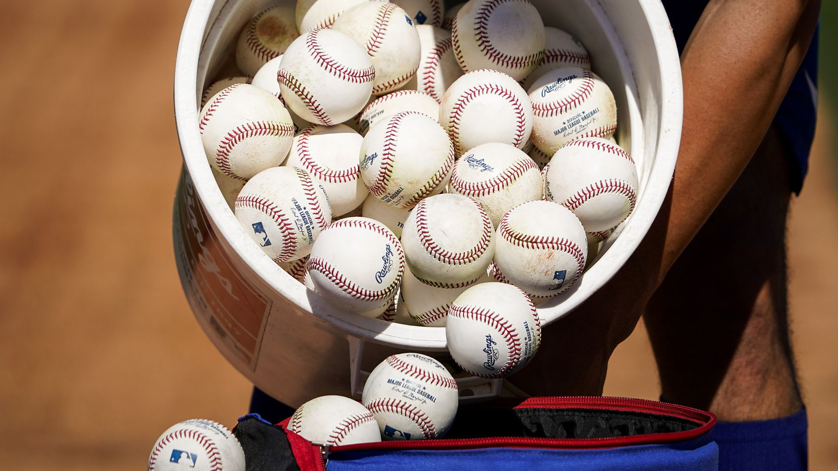 A bucket of baseballs from infield practice during a spring training workout at the Rangers' training facility on Thursday, Feb. 13, 2020, in Surprise, Ariz.