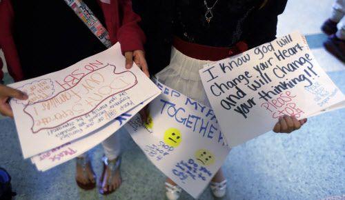 """Estudiantes distribuyen letreros que dicen """"Mantengan a mi familia unida"""" y """"Se que la buena voluntad va a cambiar su corazón y su forma de pensar"""" en el Capitolio texano, donde se aprobó ley SB4. (Eric Gay/AP)"""
