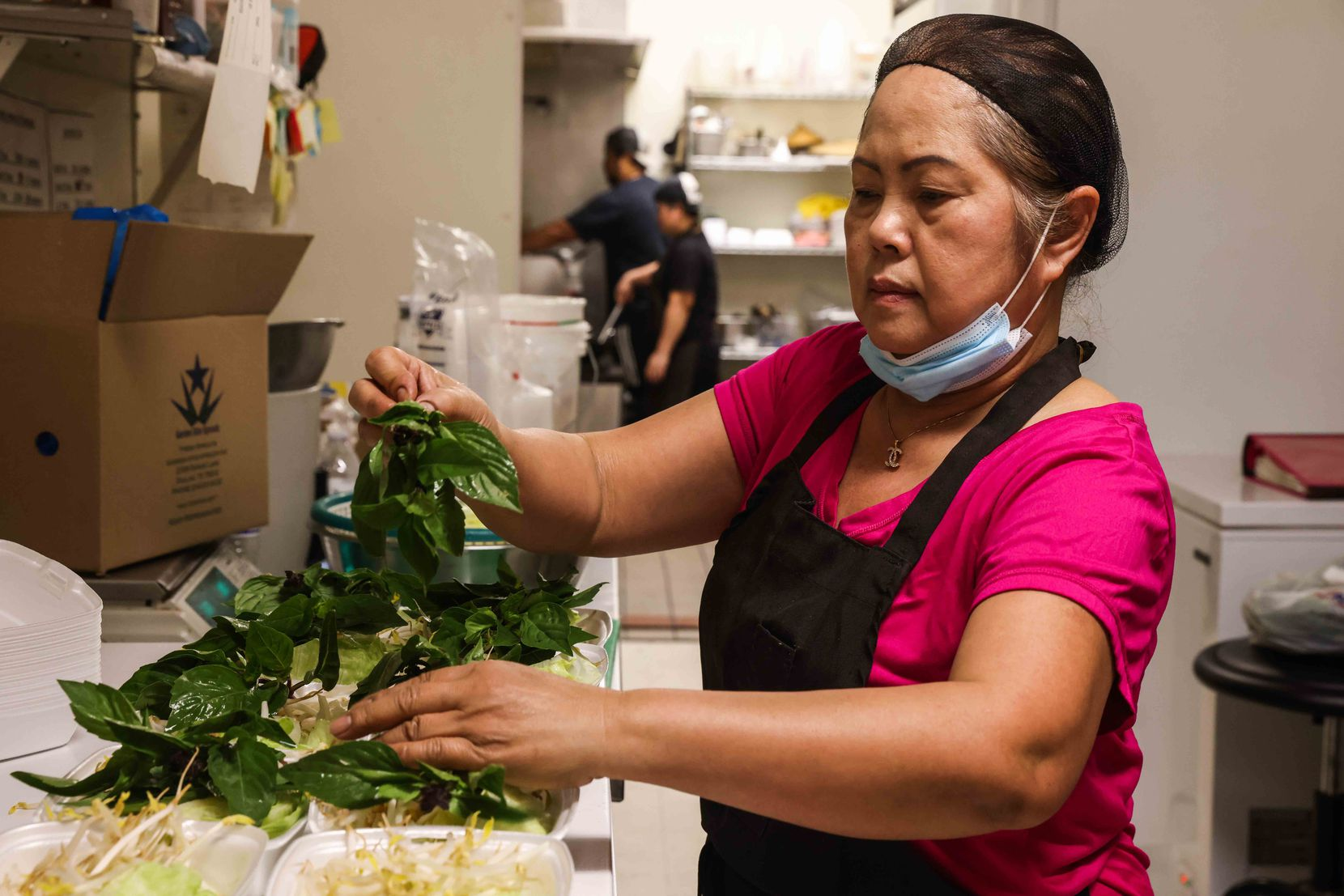 Ly Southammavong prepares some meals from the to-go menu that they offer at Ly Food Market in Oak Cliff.