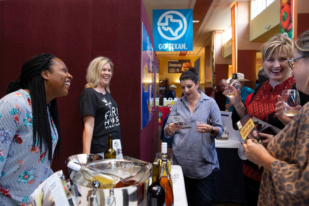 Cheramie Law, left, and Traci Ferguson, middle, of Farmhouse Vineyards promote their wines at the Go Texan Pavilion at State Fair of Texas in Dallas.