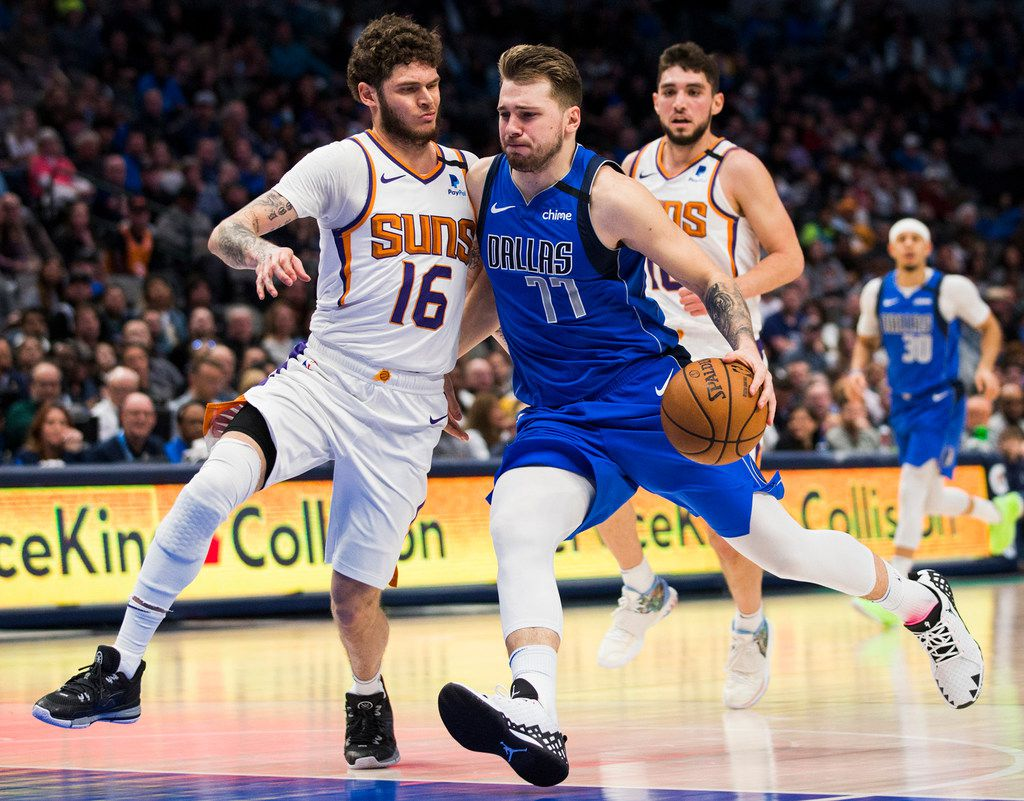 Dallas Mavericks guard Luka Doncic (77) is fouled by Phoenix Suns guard Tyler Johnson (16) during the fourth quarter on Tuesday, Jan. 28, 2020 at the American Airlines Center in Dallas, Texas. (Ashley Landis/The Dallas Morning News/TNS)