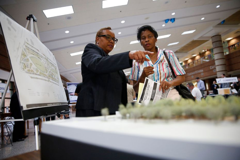 Sandra Williams (left), environmental specialist with TxDOT, speaks to Linda Smith, an Oak Cliff resident, before a public hearing on the proposed Oak Cliff Deck Park at Yvonne A. Ewell Townview Magnet Center in Dallas on April 25. The deck park, similar to Klyde Warren Park, would be over Interstate 35E in Oak Cliff.