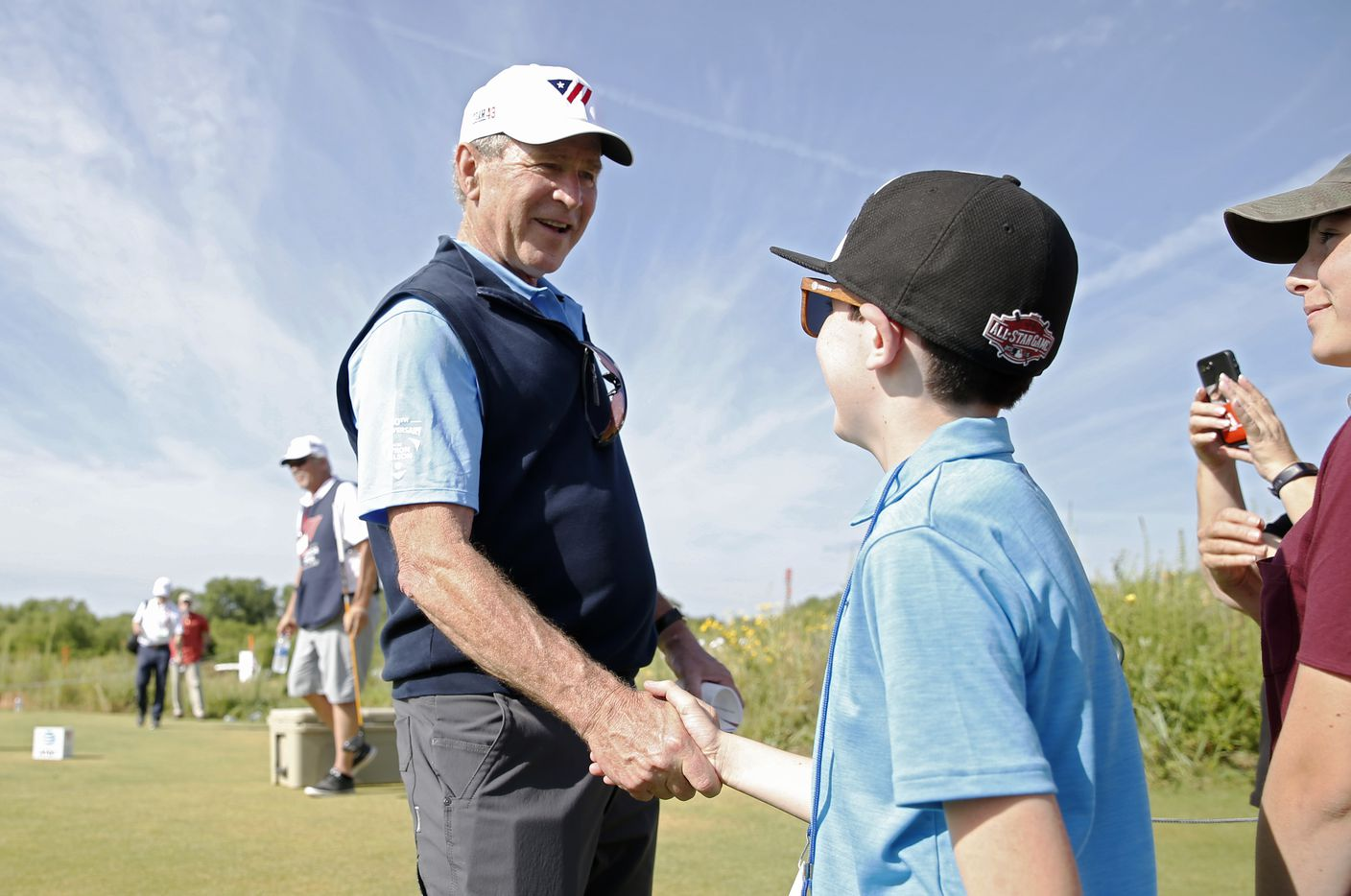 Jacob Bachelder shakes hands with George W. Bush, 43rd president of the United States during the Warrior Open at the Trinity Forest Golf Club in Dallas.