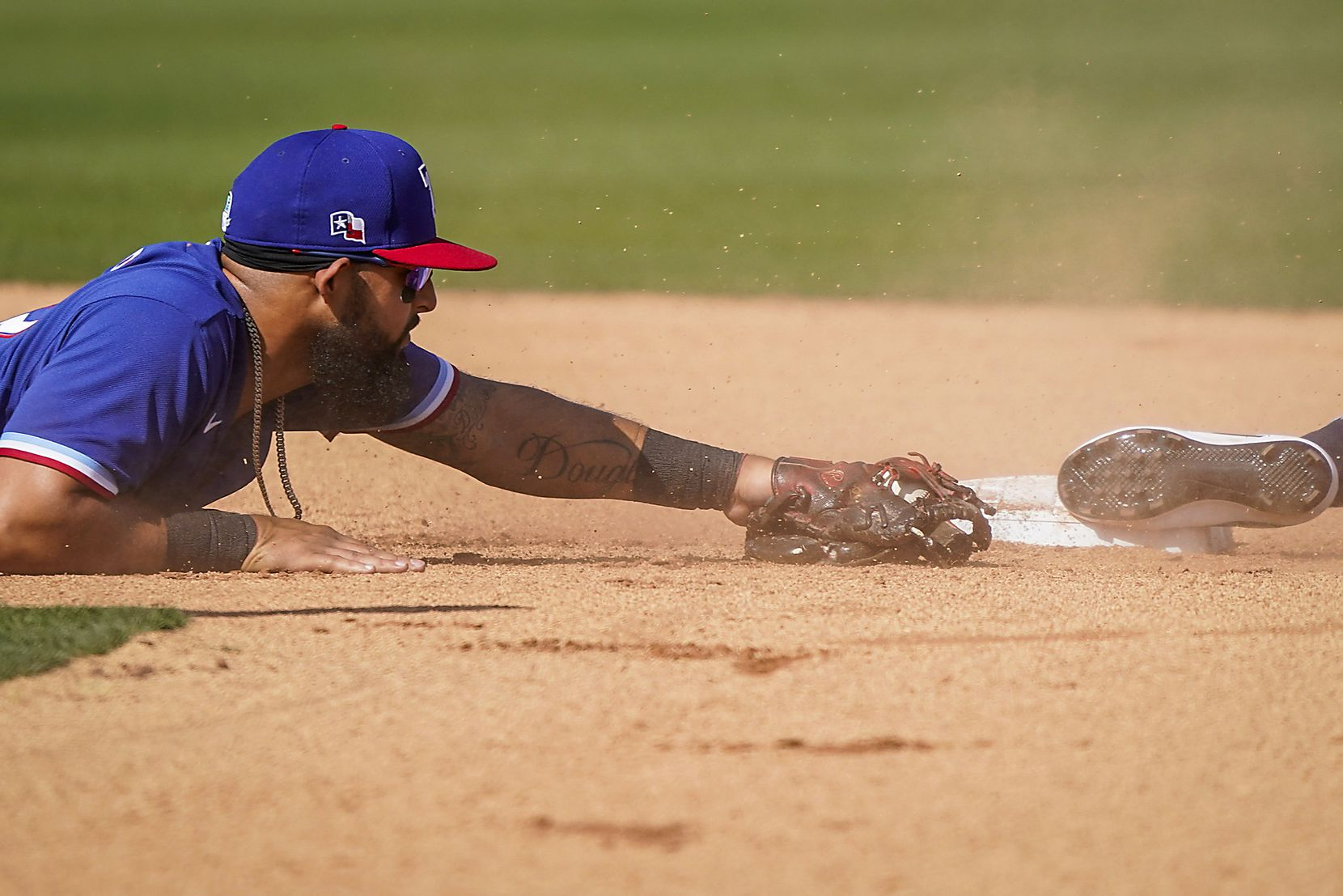 The Rangers' Rougned Odor can't make a diving tag in time as Seattle's Jordan Cowan steals second during a spring game in Peoria, Ariz.