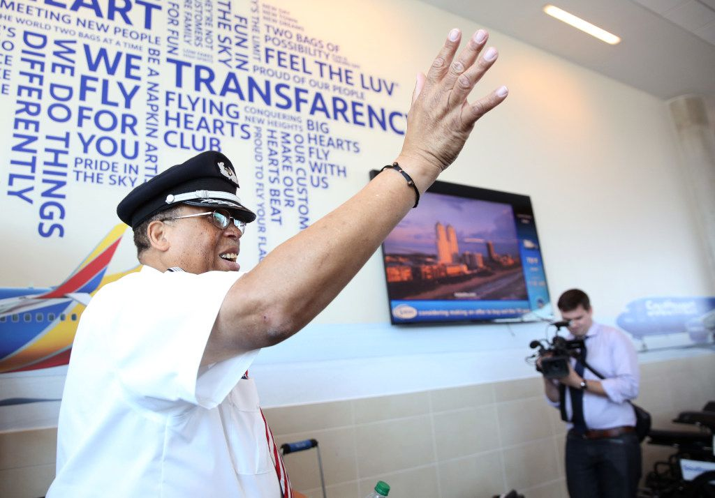 Southwest Airlines' senior pilot Lou Freeman, the first African American chief pilot of a major U.S. airline, waves goodbye to friends, family and passengers before boarding his final flight at Dallas Love Field airport in Dallas on Thursday, June 8, 2017. (Rose Baca/The Dallas Morning News)