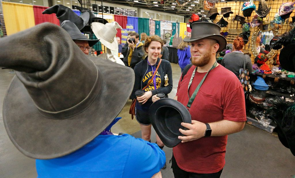 Alex Syms of Amarillo, Texas tries on a hat at a booth at LeakyCon.