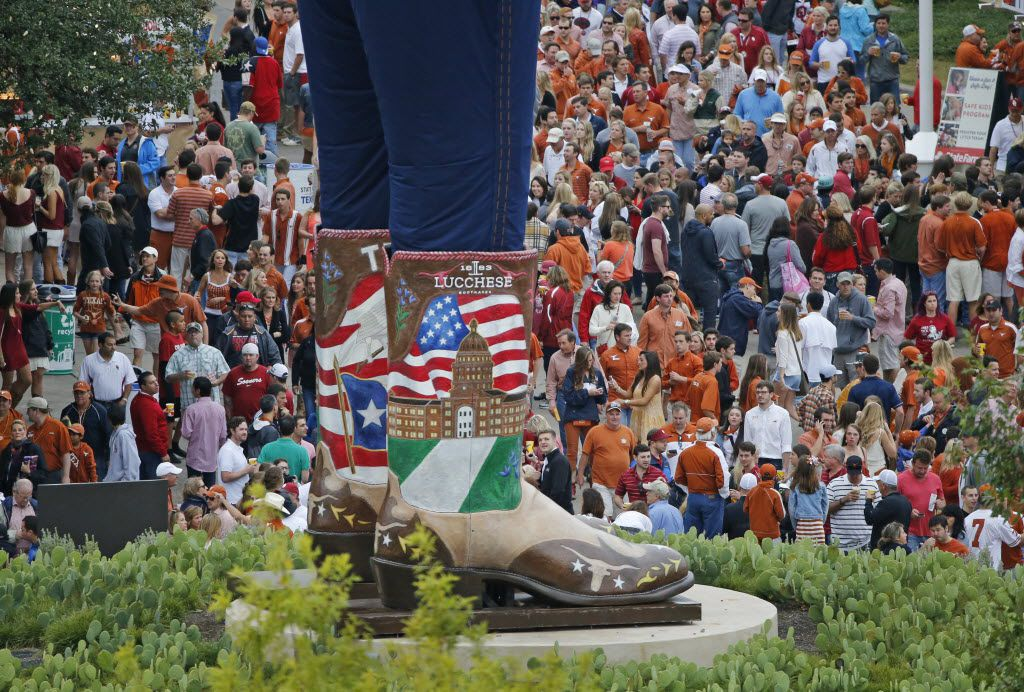 Texas and Oklahoma fans walk past the boots of Big Tex as they make their way to the stadium before the Oklahoma University Sooners vs. the University of Texas Longhorns NCAA football game at the Cotton Bowl in Dallas on Oct. 11, 2014.  (Staff Photo)