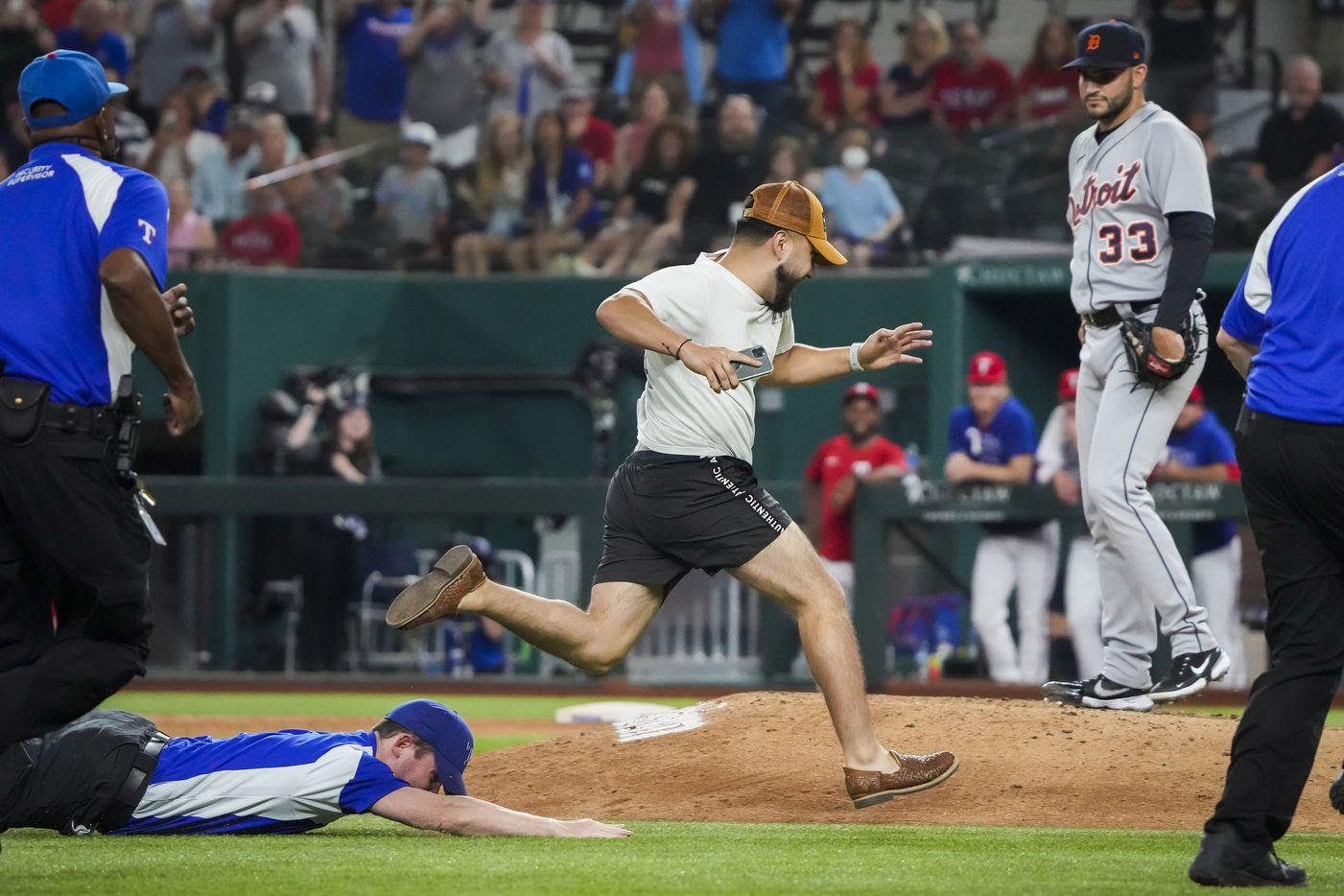 Security guards give chase to a fan who ran out on the field as Detroit Tigers relief pitcher Bryan Garcia (33) looks on during the eighth inning against the Texas Rangers at Globe Life Field on Tuesday, July 6, 2021.