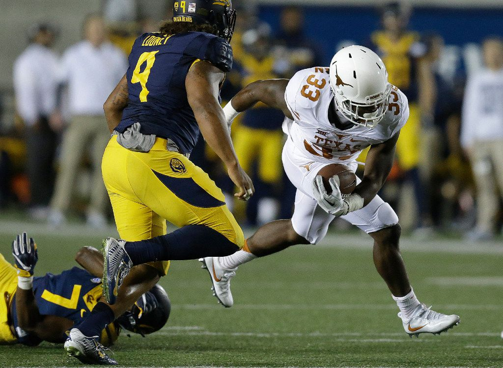 Texas running back D'Onta Foreman (33) breaks the tackle of California's Khari Vanderbilt (7) and James Looney (9) during the first quarter of an NCAA college football game Saturday, Sept. 17, 2016, in Berkeley, Calif. (AP Photo/Ben Margot)