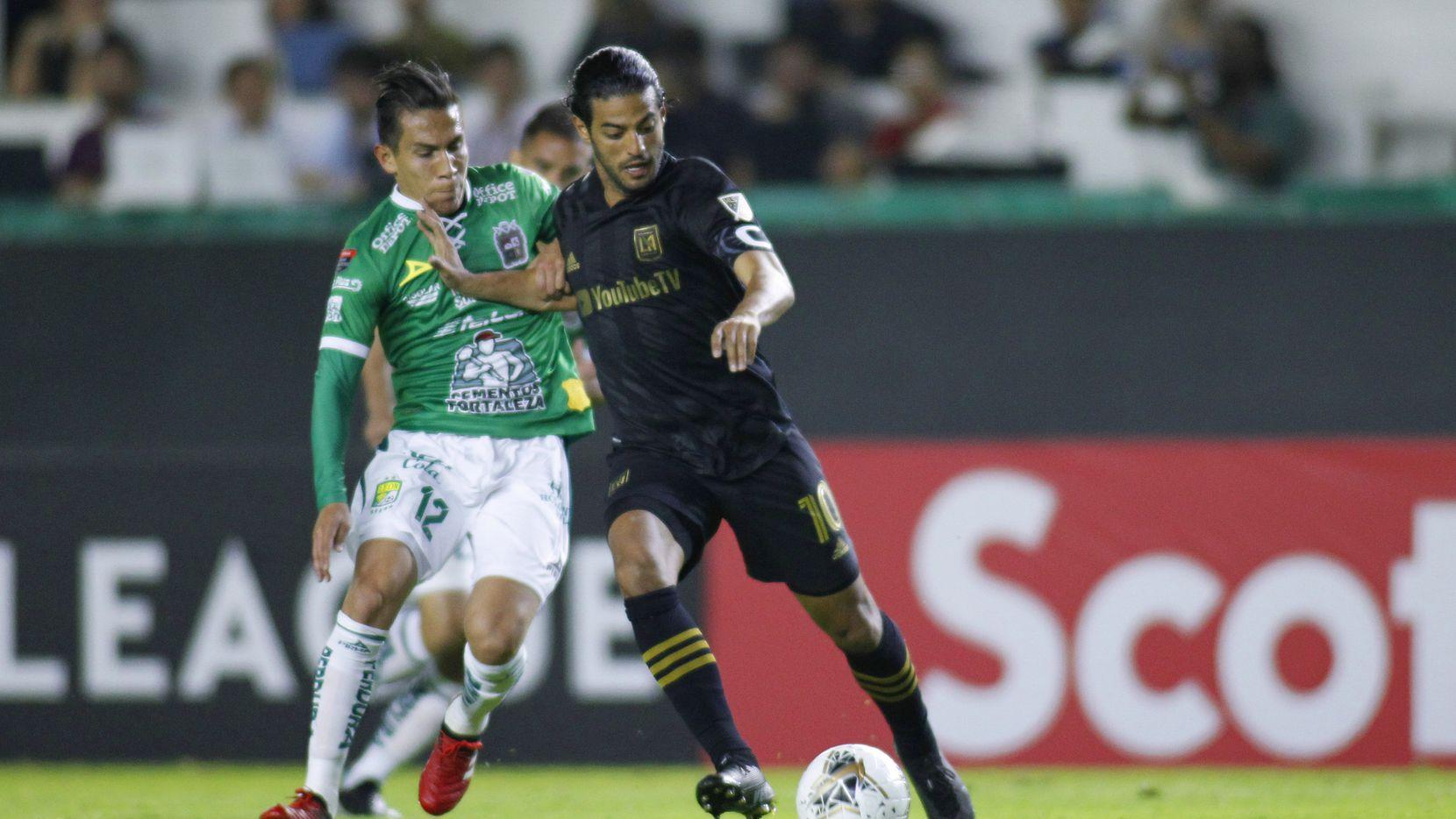 El jugador del LAFC, Carlos Vela (der), protege el balón ante la marca del jugador del León, Iván Rodríguez, durante el encuentro de la Liga de Campeones de la Concacaf, 18 de febrero en León.