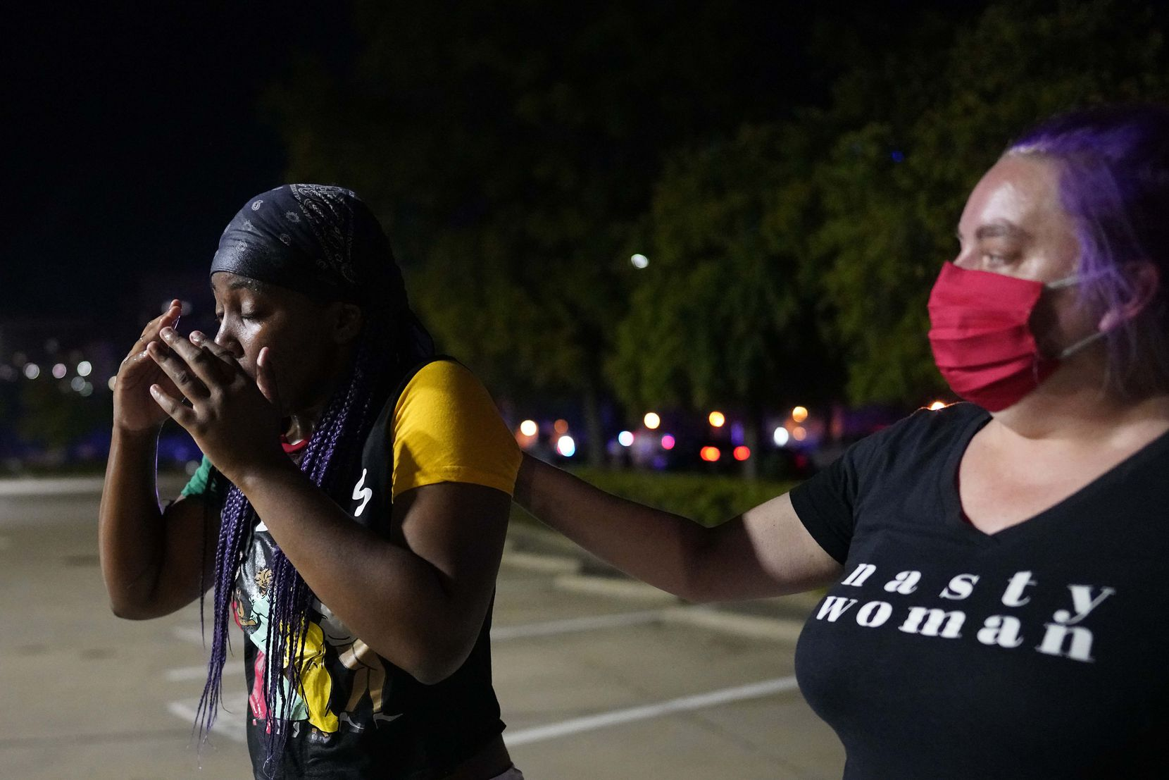 A protester is assisted after Dallas police attempted to disperse protesters with teargas at the corner of Lamar and Young Streets as they march against police brutality on Friday, May 29, 2020, in Dallas.