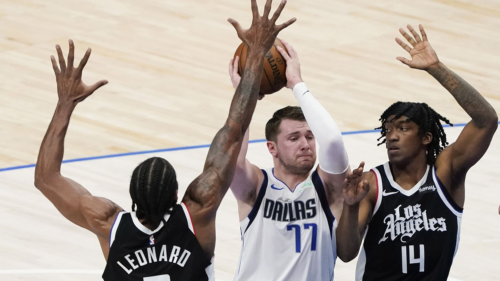 Dallas Mavericks guard Luka Doncic (77) tries to drive between LA Clippers forward Kawhi Leonard (2) and guard Terance Mann (14) during the second quarter of an NBA playoff basketball game at American Airlines Center on Sunday, May 30, 2021, in Dallas.