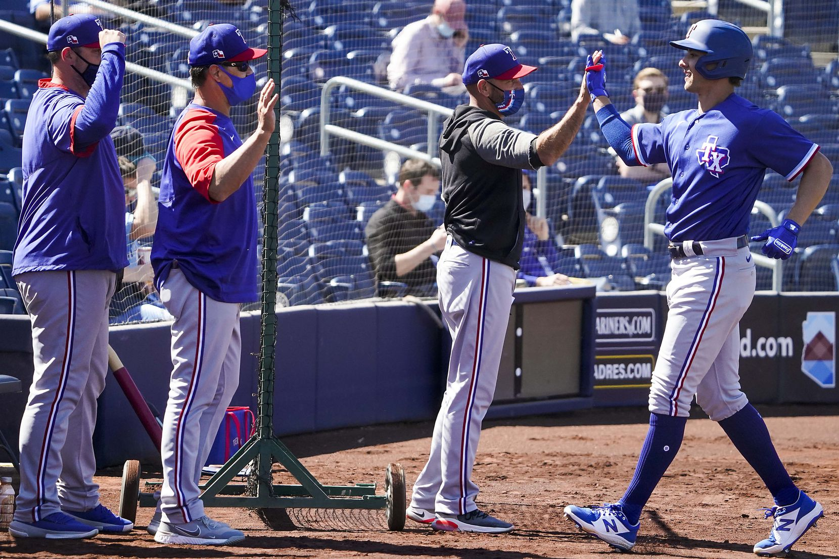 Texas Rangers outfielder Eli White (right) celebrates with manager Chris Woodward after hitting a 2-run home run during the second inning of a spring training game against the Seattle Mariners at Peoria Sports Complex on Wednesday, March 10, 2021, in Peoria, Ariz.