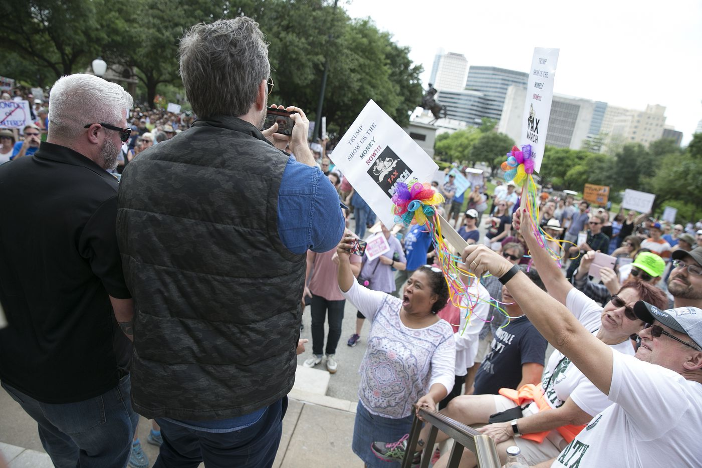 A Trump supporter, center, records video as people yell at him as he is led off stage during an encounter with those in attendance at a protest calling for President Donald Trump to release his tax returns at the Capitol in Austin, Texas, on Saturday, April 15, 2017. The protest is part of a series of marches and protest happening throughout the country. The Trump supporter jumped on stage and started yelling statements about former President Clinton.