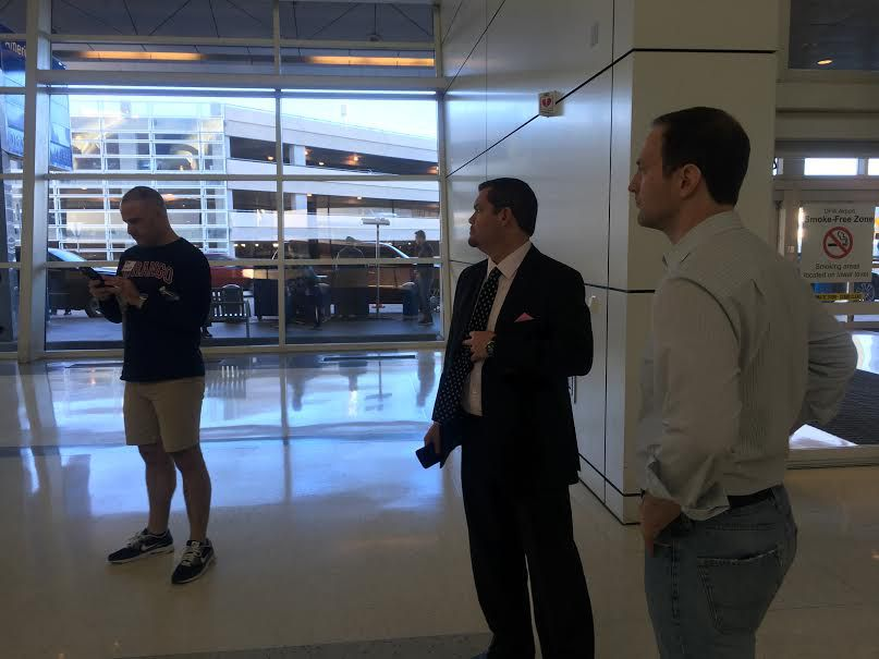 Lawyers Pete Schulte, left, Carlos Cortez, center and Perrin Fourmy pause while volunteering at D-FW International Airport Sunday.