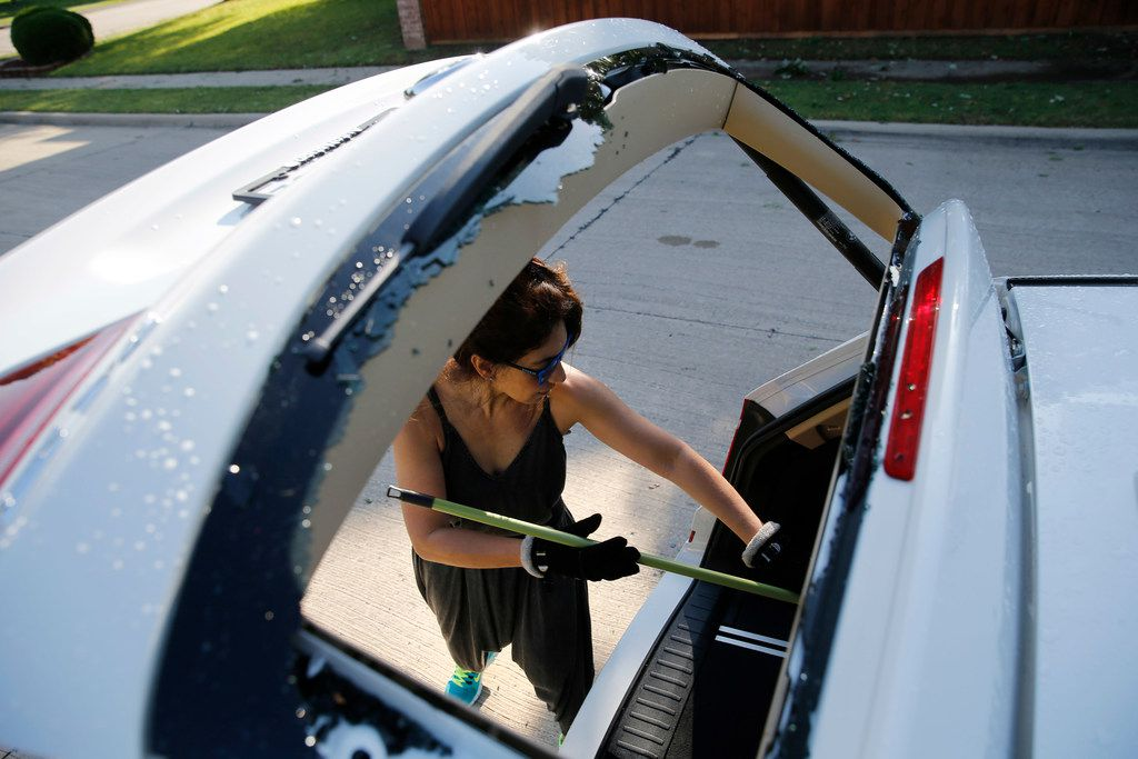 Genny Phillippe of Coppell works on cleaning broken glass from the back window of her vehicle outside her home in Coppell on Wednesday. Early morning hail storms damaged several areas in the Dallas-Fort Worth area.