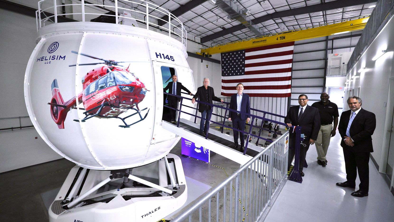 Officials, including Grand Prairie mayor Ron Jenson who is second from the left, stand in front of a newly operational flight simulator located at Airbus Helicopters headquarters.