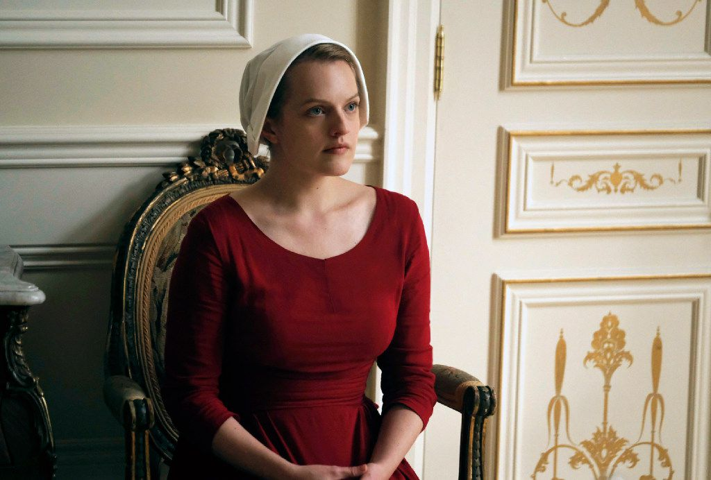 """This image released by Hulu shows Elisabeth Moss as Offred in a scene from, """"The Handmaid's Tale,"""" premiering Wednesday on Hulu with three episodes. The remaining seven hours will be released each Wednesday thereafter. (George Kraychyk/Hulu via AP)"""