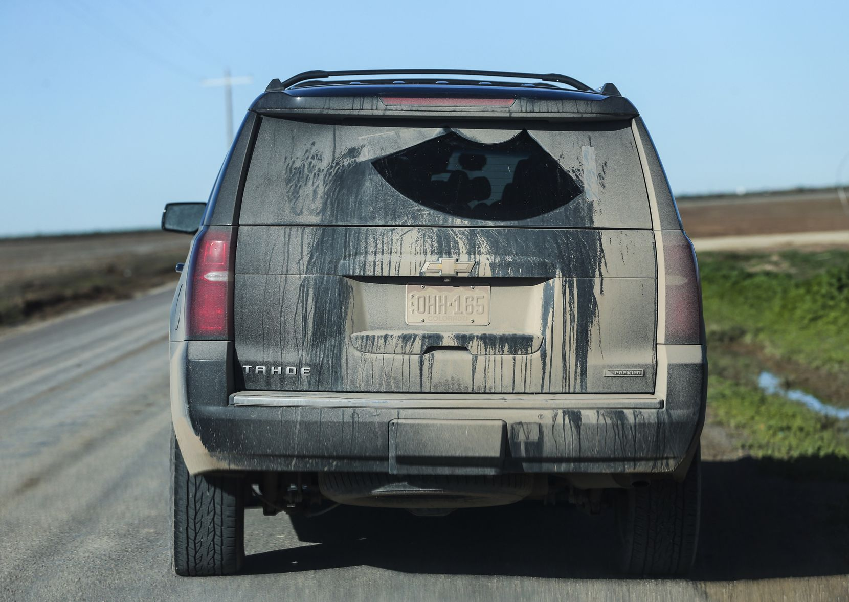Dust cakes the back of Sharon Wilson and Alan Septoff's  black rental SUV as they ply Permian Basin backroads looking for emission violations.