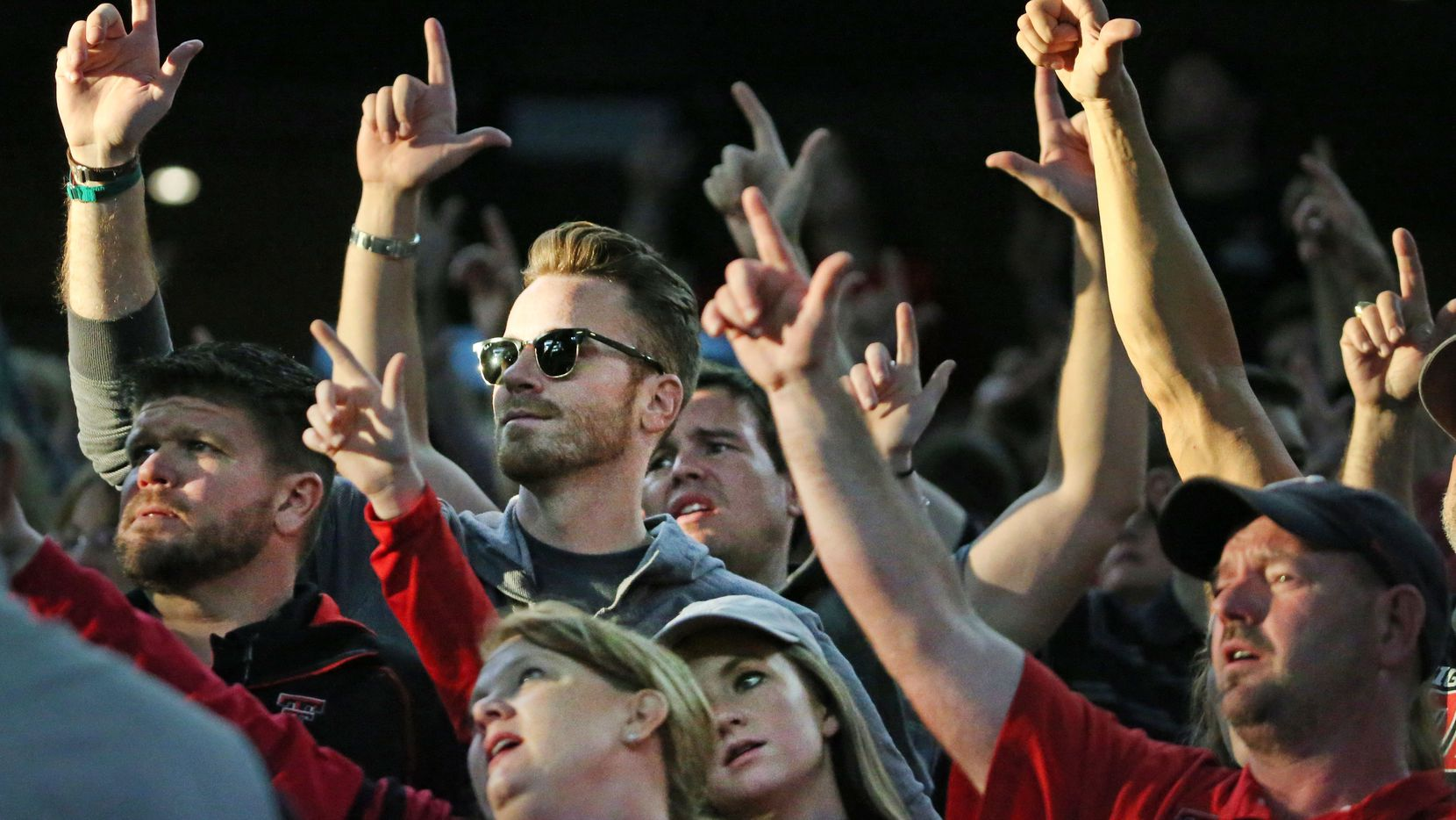 "Texas Tech fans go ""guns up"" before kickoff during the Baylor University Bears vs. the Texas Tech University Red Raiders NCAA football game at AT&T Stadium in Arlington."