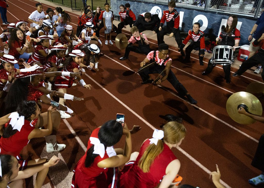 """The Bishop Dunne Catholic School Falcon Band and cheerleaders perform """"Funktrain,"""" a winning-game ritual they did after their team defeated All Saints' Episcopal School at Young Field McNair Stadium in Fort Worth, Texas, on Friday, Sep. 27, 2019. (Lynda M. Gonzalez/The Dallas Morning News)"""
