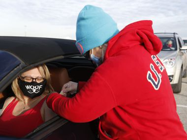 Sally Pratt of Denton gets bandage after receiving a COVID-19 vaccine shot from Penny Mayo, LVN, at a drive-through vaccination clinic at Texas Motor Speedway on Feb. 2, 2021 in Fort Worth. Fort Worth ISD has partnered with the city of Fort Worth to open a drive-through vaccination clinic at Herman Clark Stadium.