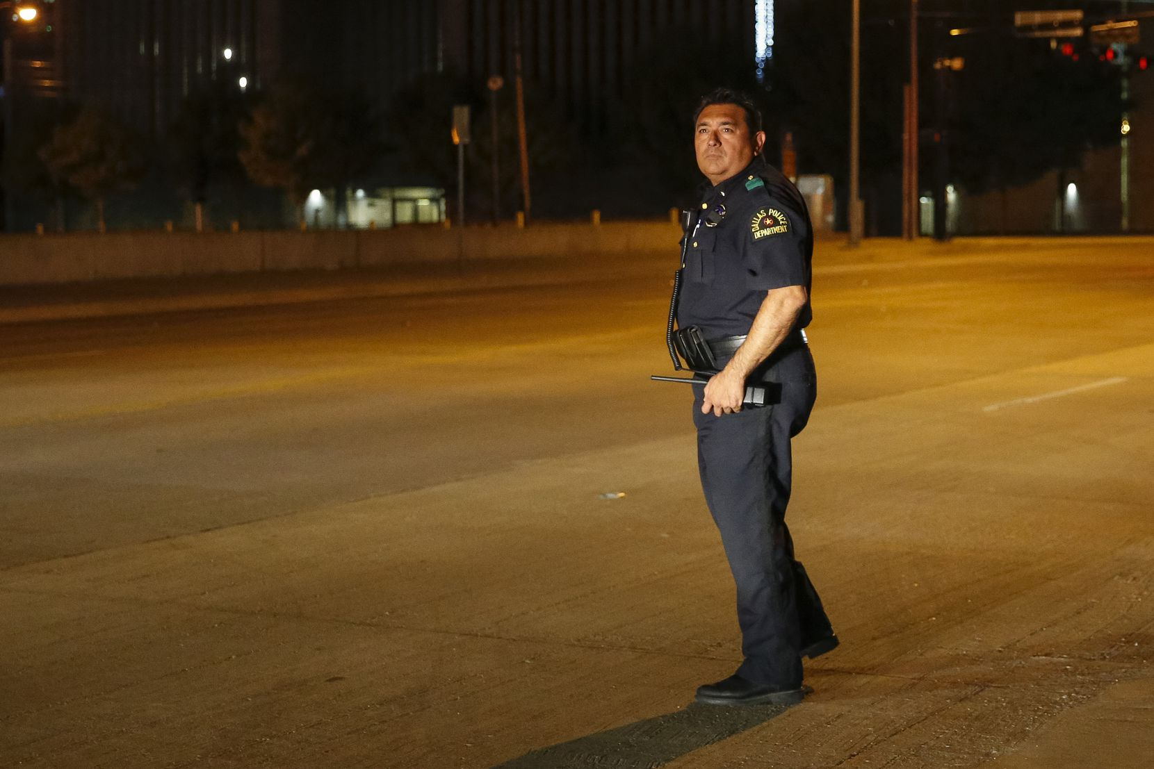 Dallas Police Deputy Chief Israel Herrera searches for bullet casings and other evidence at a shooting scene in downtown Dallas on Friday, Sept. 24, 2021.