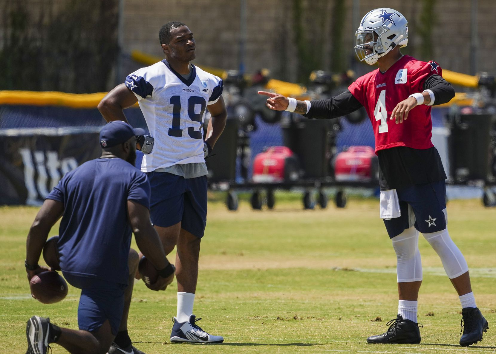 Dallas Cowboys quarterback Dak Prescott (4) works with wide receiver Amari Cooper (19) to the side of a practice at training camp on Tuesday, Aug. 10, 2021, in Oxnard, Calif.