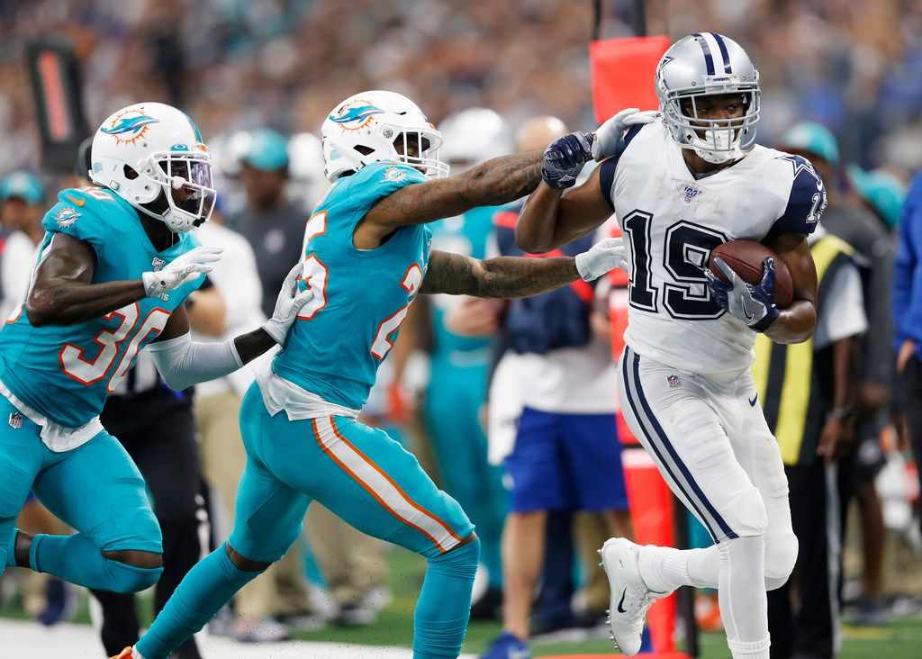 Dallas Cowboys wide receiver Amari Cooper (19) is pushed out of bounds after the catch by Miami Dolphins cornerback Xavien Howard (25) as Miami Dolphins defensive back Chris Lammons (30) closes in on the play during the second half of play at AT&T Stadium in Arlington, Texas on Sunday, September 22, 2019. The Dallas Cowboys defeated the Miami Dolphins 31-6.