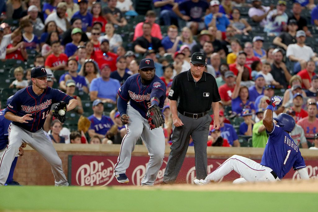 ARLINGTON, TEXAS - AUGUST 16: Elvis Andrus #1 of the Texas Rangers slides into third base against Jake Odorizzi #12 of the Minnesota Twins and Miguel Sano #22 of the Minnesota Twins in the bottom of the third inning at Globe Life Park in Arlington on August 16, 2019 in Arlington, Texas. (Photo by Tom Pennington/Getty Images)