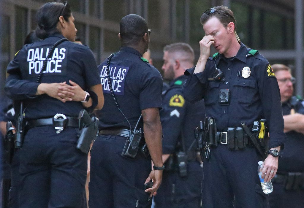 Dallas Police officers are pictured waiting outside at the entrance to the emergency room at Presbyterian Hospital in Dallas. Two Dallas policemen were reportedly shot at a nearby Home Depot and reportedly were transported to the Dallas hospital on Tuesday, April 24, 2018.